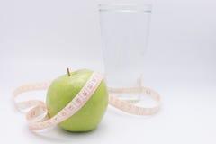 Una mela verde con nastro adesivo di misurazione lo ha avvolto per il co Fotografia Stock Libera da Diritti