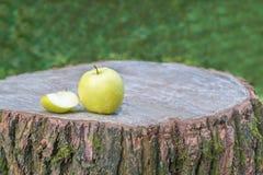 Una mela verde su un ceppo di legno Fotografia Stock