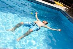 Una mentira del hombre cara arriba en una piscina del agua clara Imagen de archivo