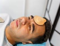 Una menzogne paziente su una barella con un magnete sulla sua fronte fotografia stock