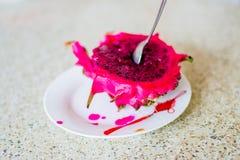 Una metà della frutta del drago su un piatto con il cucchiaio Fotografia Stock