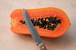 Una metà della papaia ha tagliato dal coltello tagliente sulla parete di legno Fotografie Stock
