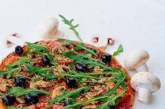 Una metà della pizza della verdura con il rucola, pomodori, olive nere sui precedenti bianchi decorati con i funghi freschi Immagini Stock