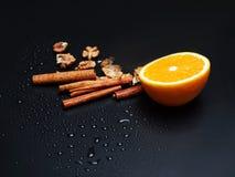 Una metà di arancio, dei dadi e della cannella su un fondo scuro, primo piano Fotografie Stock