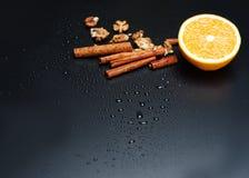 Una metà di arancio, dei dadi e della cannella su un fondo scuro, primo piano Immagine Stock Libera da Diritti