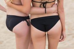 Una metà di sezione di due giovani donne del bikini alla spiaggia Fotografie Stock