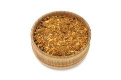 Una mezcla de pimientas en un cuenco de madera Foto de archivo
