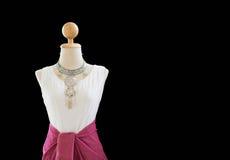Una mezza lunghezza dei vestiti tradizionali tailandesi sul manichino con fondo nero Immagine Stock