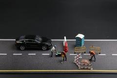 una mini figura con il segnale di pericolo sulla via concreta incrinata Immagine Stock