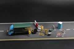 una mini figura con il segnale di pericolo sulla via concreta incrinata Fotografie Stock Libere da Diritti