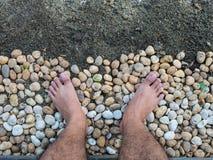Una mirada del hombre abajo a sus pies, soporte en las rocas Fotos de archivo libres de regalías