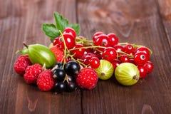 Una miscela delle bacche mature su una tavola di legno Di estate vita ancora Lamponi, uva spina, primo piano dell'uva passa Immagine Stock