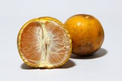 Una mitad de la naranja pelada y de una naranja no pela aislado en el fondo blanco Fotos de archivo libres de regalías