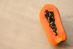 Una mitad de la papaya en la pared de madera Foto de archivo libre de regalías