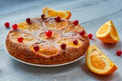 Una mitad de la torta anaranjada hecha en casa adornada con los arándanos rojos frescos y las rebanadas anaranjadas en el fondo g Imagen de archivo