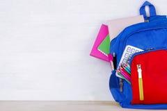 Una mochila de la escuela con las fuentes de escuela en un fondo de madera blanco con un lugar para una inscripción imagen de archivo