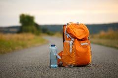 Una mochila para una cámara anaranjada y una botella de agua en una carretera de asfalto en un campo Imágenes de archivo libres de regalías