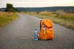 Una mochila para una cámara anaranjada y una botella de agua en una carretera de asfalto en un campo Imagen de archivo