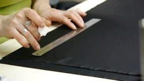 Una modista que corta un negro de alta calidad de la tela, antes de que usted lo cosa y haga un pedazo de la ropa de la alta moda almacen de video