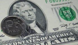 Una moneda con una muestra de la rublo descansa sobre un billete de dólar dos Imagen de archivo libre de regalías