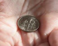 Una moneda de diez centavos americana en la palma de una hembra da A Imagen de archivo libre de regalías