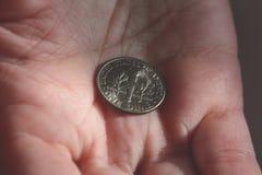 Una moneda de diez centavos americana en la palma de una hembra da B Imagenes de archivo