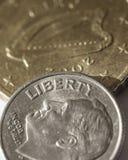 Una moneda de diez centavos americana encima de una moneda Fotografía de archivo