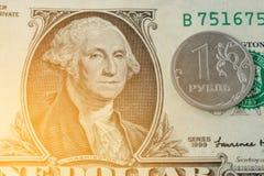 Una moneda de la rublo en billete de banco del dólar Foto de archivo
