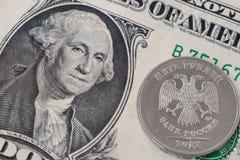 Una moneda de la rublo en un billete de banco del dólar Fotografía de archivo libre de regalías