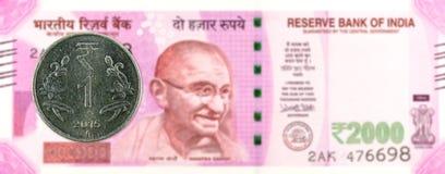 Una moneda 2015 de la rupia contra 2000 billetes de banco de la rupia india fotografía de archivo libre de regalías