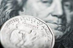 Una moneda del dólar en los cientos billetes de dólar Fotografía de archivo libre de regalías