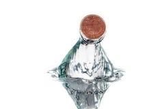 Una moneda del penique cogida perfectamente en chapoteo del agua Foto de archivo libre de regalías