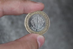 Una moneda digno de 1 lira turca entre los fingeres de la mano Foto de archivo libre de regalías