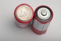 Una moneda euro encima de la batería Foto de archivo libre de regalías