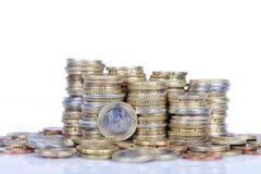 Una moneda euro situada delante de más monedas aisladas Imágenes de archivo libres de regalías