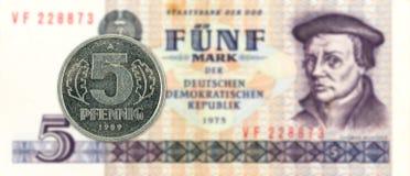 una moneta da 5 pfennig contro la banconota storica del segno di 5 tedeschi orientali fotografia stock