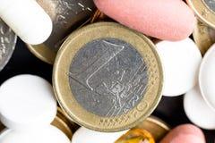 Una moneta da un euro nel mezzo di medicina Fotografie Stock Libere da Diritti