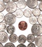 Una moneta del penny tra altre monete. Fotografie Stock