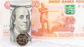 Una moneta della rublo russa contro una banconota da 100 dollari americani Fotografie Stock Libere da Diritti
