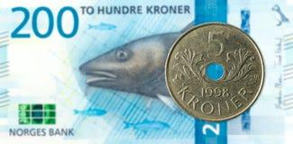 una moneta di 5 norvegesi contro una nuova banconota di 200 corone norvegesi fotografia stock libera da diritti