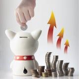 Una moneta di risparmio della mano in banca piggy Immagine Stock