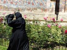 Una monja vista de detrás con las manos levantó en un monasterio del Bucovina en Rumania fotos de archivo