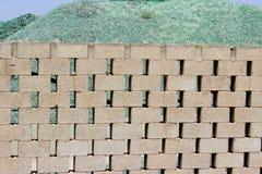 Una montaña de pequeños fragmentos del vidrio verde detrás de una pared de ladrillo Imagen de archivo libre de regalías