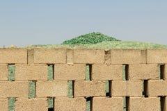 Una montaña de pequeños fragmentos del vidrio verde detrás de una pared de ladrillo Fotografía de archivo
