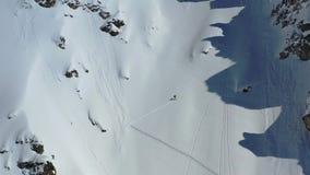 Una montaña masiva cubrió en nieve fresca, un hombre en los esquís la está subiendo, cantidad aérea metrajes