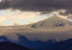 Una montagna nevosa circondata dalle nuvole bianche e scure Fotografia Stock