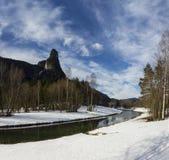 Una montagna scenica e un chiaro fiume con neve Fotografia Stock