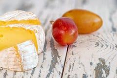 Una morbidezza ha maturato il formaggio e l'uva del camembert su un bordo di legno anziano Fine in su immagine stock libera da diritti