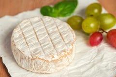 Una morbidezza ha maturato il formaggio e l'uva del camembert su un fondo bianco fotografie stock libere da diritti