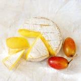 Una morbidezza ha maturato il formaggio e l'uva del camembert su un fondo bianco fotografia stock libera da diritti